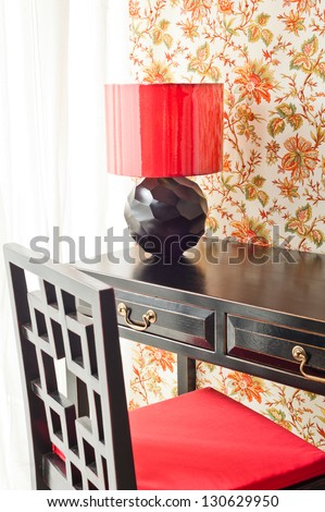Luxury work desk with floral wallpaper next to bright window - stock photo