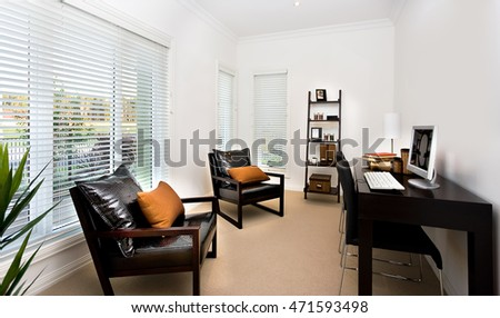 Luxury work room has windows fixed to the white wall, the dark wooden table near the wall has a computer and few books neat the white lamp. There are two chairs and pillows near the table