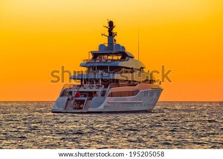 Luxury yacht on open sea at golden sunset - stock photo