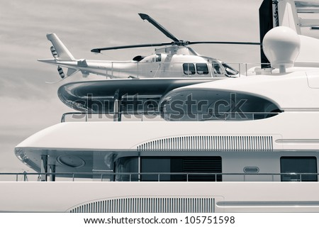 Luxury yacht with helicopter on the deck, digitally retouched and toned photo. - stock photo