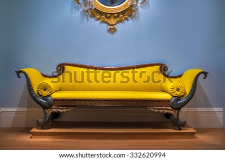 Luxury yellow sofa in front of the blue wall - stock photo