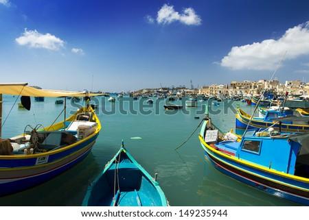 Luzzu Boats in Marsaxlokk Port in Malta - stock photo