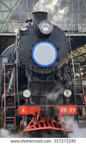 LVIV, UKRAINE - DECEMBER, 2015: Old Soviet vintage black retro train L-3535 at the railway station in Lviv produces steam from the pipes  - stock photo