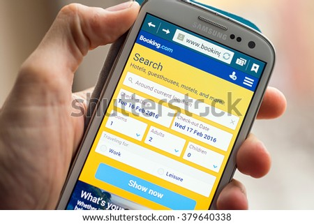 LVIV, UKRAINE - Feb 16, 2016: Hand holding white Samsung Smart Phone with booking.com site on screen, booking.com  is a popular online reservation hotels site - stock photo