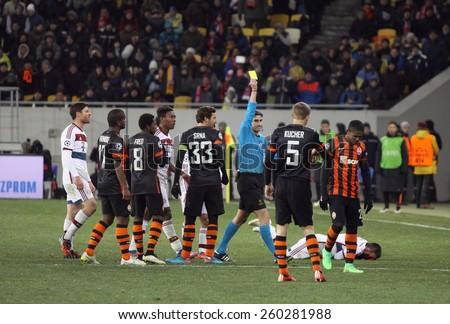 LVIV, UKRAINE - FEBRUARY 17, 2015: Referee shows yellow card during UEFA Champions League game between Shakhtar Donetsk and Bayern Munich at Arena Lviv stadium - stock photo