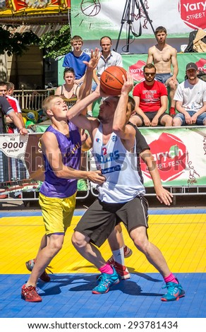Lviv, Ukraine - July 2015: Yarych street Fest 2015. Street basketball competition at the festival near Lviv Opera House. Players fight for the ball under the basket