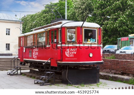 "LVIV, UKRAINE - MAY 8, 2016:  A touristic tram near ""The Arsenal"" which is a shop to buy different things and souvenirs and also coffee, Lviv, Ukraine"