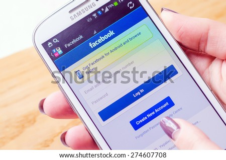 LVIV, UKRAINE - May 03, 2015: Hand holding white Samsung Smart Phone with Facebook Social Network Log In Screen - stock photo