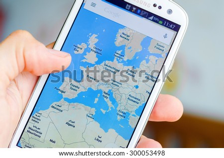 LVIV, UKRAINE - May 19, 2015: Hand holding white Samsung Smart Phone with Google map application - stock photo