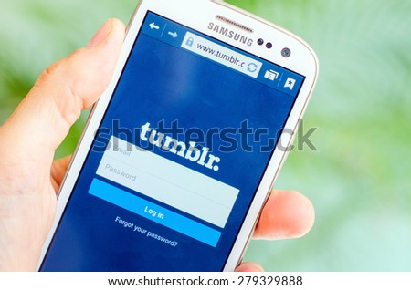 LVIV, UKRAINE - May 19, 2015: Hand holding white Samsung Smart Phone with Tumblr social Network Log In Screen - stock photo
