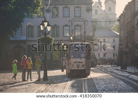 LVIV, UKRAINE - MAY 6, 2016: Morning streets of Lviv city. Old tram at street of the old city center. - stock photo