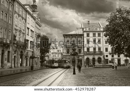 LVIV, UKRAINE - MAY 8, 2016:  The center of Lviv - The Market Square. Two trams passing along the street. Black and white photo. Ukraine