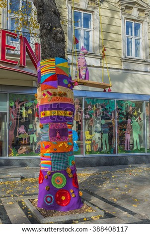 LVIV, UKRAINE - OCT 26, 2015: Wood put big beautiful scarf tied by hand and the thread violet cat toy in the city center. Picture taken in the morning during a trip to Lviv.