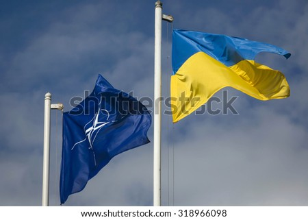 "LVIV, UKRAINE - Sep 21, 2015: The national flag of Ukraine and NATO flag during the opening the teaching of the Ukraine-NATO disaster relief ""Ukraine-2015"" - stock photo"