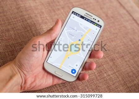 LVIV, UKRAINE - Sept 09, 2015: Hand holding white Samsung Smart Phone with Google map application - stock photo