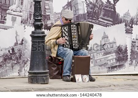 LVOV, UKRAINE - APRIL 25: Street musician in the center of Lvov entertain tourists on April 25, 2013 in Lviv, Ukraine - stock photo
