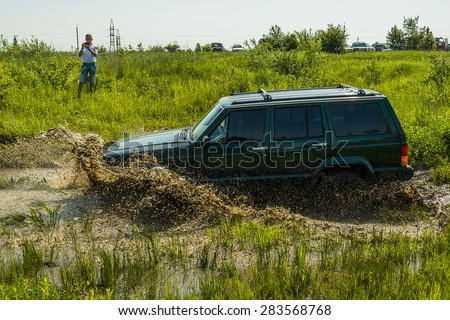 Lvov, Ukraine - May 30, 2015: Off-road vehicle Jeep Cherokee  overcomes the track on  of   landfill near the city  Lvov, Ukraine. - stock photo