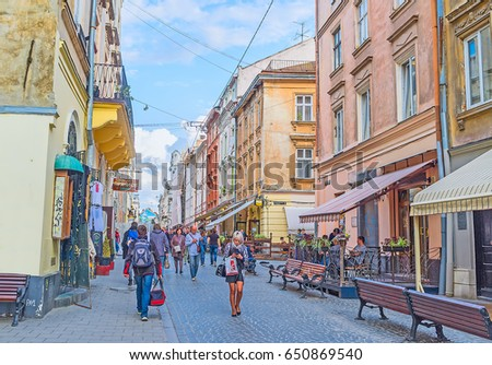 LVOV, UKRAINE - MAY 16, 2017: The crowded Krakivska street with numerous benches for tired tourists, cozy cafes and coffee shops, on May 16 in Lvov.