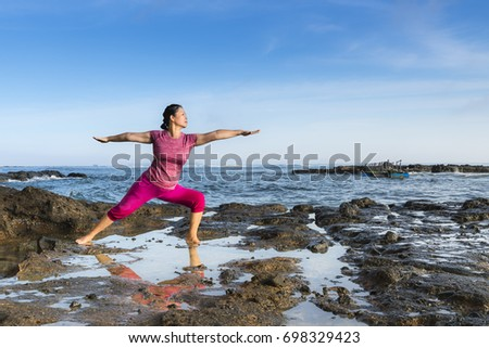 Ly Son Island, Quang Ngai Province, Vietnam - July 30, 2017: A woman on the volcanic cliff is practicing yoga in the dawn light on Ly Son Island, Quang Ngai Province, Vietnam