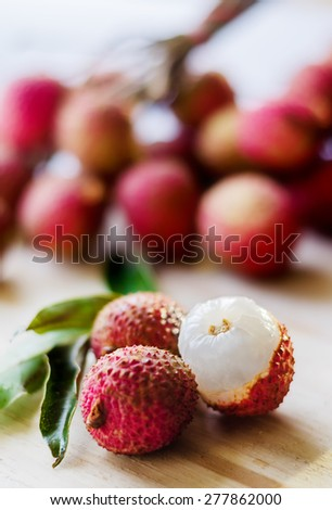 Lychee fruit with green leaves on a wooden board - stock photo
