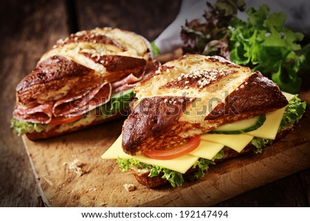 Lye bread rolls , a German and Bavarian speciality bread glazed and baked with lye, with cheese and salami with fresh lettuce, tomato and cucumber on an old wooden board - stock photo