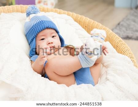Lying Asian baby in stuio backgound. - stock photo