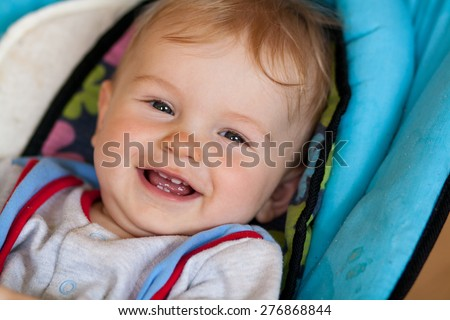 lying baby, smiling baby, baby has something in mouth, hold with teeth, lying in deck chair for baby - stock photo