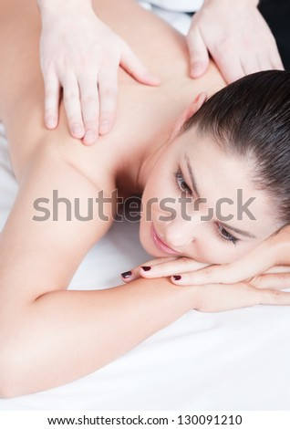 Lying brunette woman receiving massage at spa - stock photo
