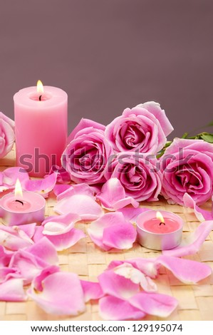 Lying down rose flowers with petals and pink candle on mat