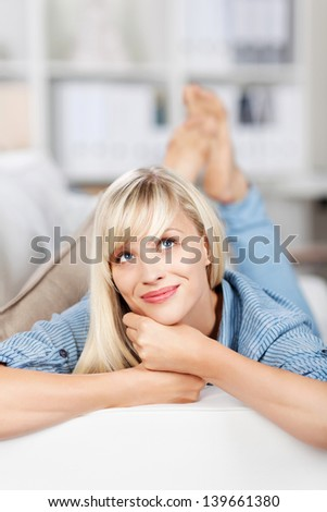 Lying female on couch having daydreaming over the blurred background - stock photo