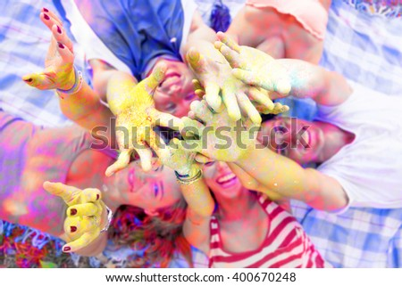 lying group of young adult pushes his hands up painted with many color - stock photo