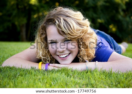 Lying in the grass and having a laugh is this cute high school graduate - stock photo