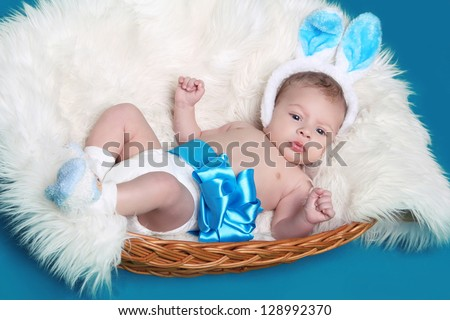 Lying newborn baby on towel over blue background