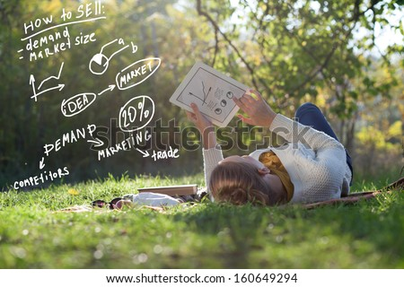 Lying woman drawing business concept on tablet pc screen during rest in the park - stock photo
