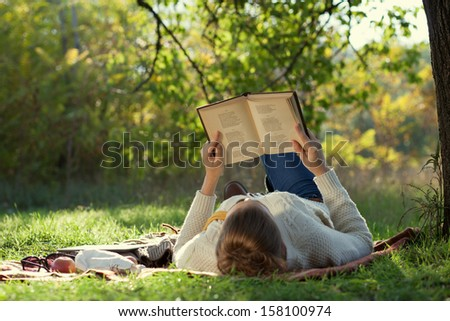 lying woman reading a book during a relax in the park. - stock photo