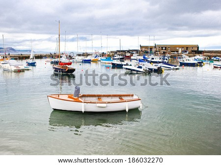 LYME REGIS, ENGLAND - APRIL 08: Boats in high tide, Lyme Regis harbour, Jurassic Coast, Dorset, England, April 08, 2012. The town is famous for the fossils found in the cliffs and beaches.