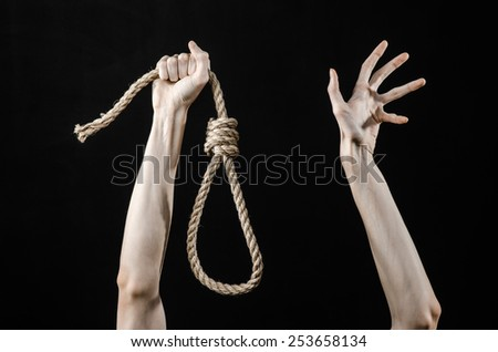 Lynching and suicide theme: man's hand holding a loop of rope for hanging on black isolated background - stock photo