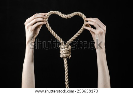 Lynching and suicide theme: man's hand holding a loop of rope for hanging on black isolated background unrequited love and broken heart - stock photo
