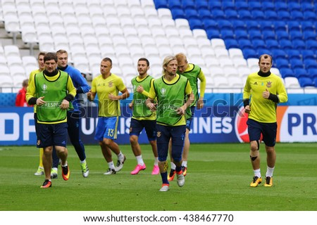 LYON, FRANCE - JUNE 15, 2016: Players run during Open training session of Ukraine National Football Team before UEFA EURO 2016 game against N.Ireland. Stade de Lyon, Lyon, France - stock photo