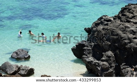LYSON ISLAND, QUANG NGAI PROVINCE, VIETNAM - JUNE 2016: Unidentified people are swimming on the blue sea of Ly Son island, besides the volcanic rocks. Ly Son is an ancient volcanic island.