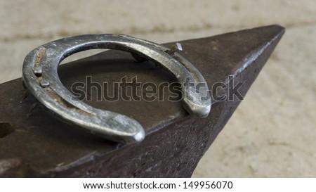 M?etallic dirty anvil and horseshoe, farrier tools - stock photo
