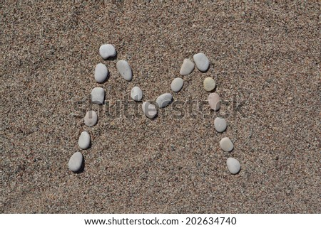 M letter made of stones on sand  - stock photo