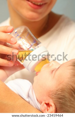 ma feeds tiny infant from bottle - stock photo