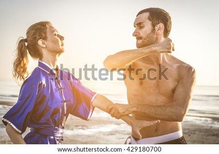 Maartial arts fight between master and his pupil at the beach during the sunrise. concept about people, lifestyle and sport - stock photo
