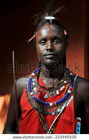 MAASAI MARA, KENYA - AUGUST 10: Maasai man in traditional clothing August 10, 2010 at Masaai Mara, Kenya. The Maasai are the most famous tribe in Africa. They are nomadic and live in small villages.. - stock photo