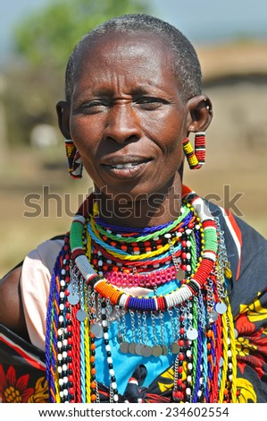 MAASAI MARA, KENYA - AUGUST 12: Maasai Woman in the village, 12 August, 2010 at Masaai Mara, Kenya. The Maasai are the most famous tribe in Africa. They are nomadic and live in small villages. - stock photo