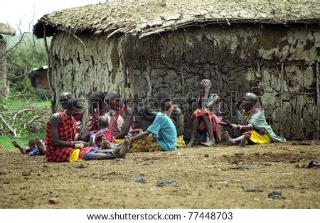 MAASAI MARA, KENYA - FEBRUARY 4: Maasai unidentified family in the village, 4 February , 2004 at Masaai Mara, Kenya. The Maasai are the most famous tribe in Africa. They are nomadic and live in small villages. - stock photo