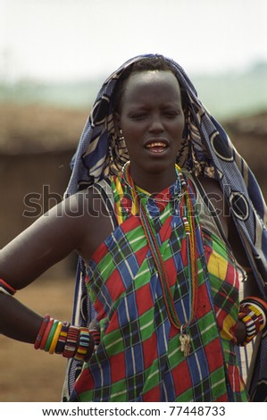 MAASAI MARA, KENYA - FEBRUARY 4: Maasai woman in the village, 4 February , 2004 at Masaai Mara, Kenya. The Maasai are the most famous tribe in Africa. They are nomadic and live in small villages. - stock photo
