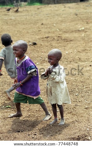 MAASAI MARA, KENYA - FEBRUARY 4: 5-6 years old unidentified children play, 4 February , 2004 at Masaai Mara, Kenya. The Maasai are the most famous tribe in Africa. They are nomadic and live in small villages. - stock photo