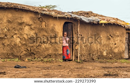 MAASAI MARA, KENYA - OCTOBER 17, 2014 : Young african girl from masai tribe in the doorway of her home. The Maasai are a Nilotic ethnic group living in southern Kenya and northern Tanzania - stock photo